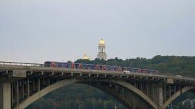 De trein reist over de brug tegen de hemel en de koepels van de kerk Buiten verlaten stadsmetro Openbaar vervoer  stock videobeelden