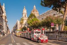 De trein van de excursiestoom op de achtergrond van de Kathedraal in Catanië Stock Foto's