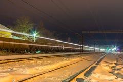 De trein van de hoge snelheidspassagier op spoorwegsporen met het effect van het motieonduidelijke beeld dichtbij het station stock foto