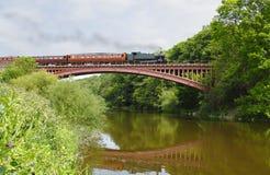 De trein van de stoom op brug stock fotografie