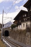 De trein verlaat de tunnel amid de Alpen en de Zwitserse huizen stock foto