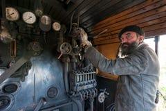 De treinbestuurder dichtbij de stoom voortbewegingsboiler stock afbeelding