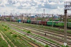 De treinen met goederen en goederenwagonnen zijn op de spoorweg stock afbeeldingen