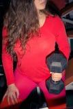 De treinen van het sportenmeisje met domoren sportenfitness en gewichtheffen Dramatische verlichting stock foto's