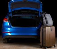De tribune van bagagezakken naast open autoboomstam stock afbeeldingen