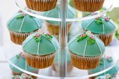 De tribune van de huwelijks cupcake toren met turkooise cakes Stock Foto
