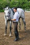 De tribune van de jockey dichtbij paard voedt hem Stock Afbeelding