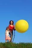 De tribune van de moeder en van de dochter in weide met ballon Stock Afbeeldingen