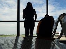 De tribune van de silhouetvrouw en kijkt buitenvenster met zak op stoel wachtende vlucht in luchthaven Alleen vrouwenreis Stock Foto