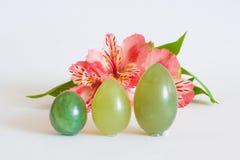 De tribune van jadeeieren dichtbij een roze bloem Stock Foto's