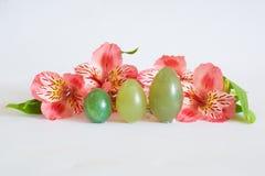 De tribune van jadeeieren dichtbij roze bloemen Stock Afbeeldingen