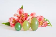 De tribune van jadeeieren dichtbij roze bloemen Stock Fotografie
