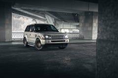 De tribune van Rover Range Rover van het autoland onder brug in de stad van Moskou bij dag Stock Foto's