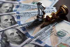 De tribune van de schaakridder over de gevallen koning met het bankbiljetachtergrond van de V.S. De stokvoering en de holdingsham stock fotografie