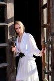 De tribunes van de blondevrouw in de oude houten deuropening De oude houten deur Jong vrouwen modern portret stock fotografie