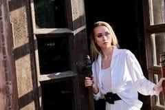 De tribunes van de blondevrouw in de oude houten deuropening De oude houten deur Jong vrouwen modern portret stock afbeelding