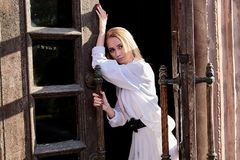De tribunes van de blondevrouw in de oude houten deuropening De oude houten deur Jong vrouwen modern portret royalty-vrije stock foto's