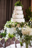 De tribunes van de huwelijkscake op de verfraaide lijst Stock Foto's