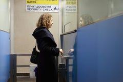 De tribunes van de vrouw in veiligheidscontrolepost bij luchthaven Stock Foto