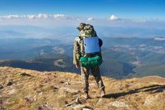 De tribunes van de wandelaar op een piek van bergen en het kijken het landschap stock fotografie