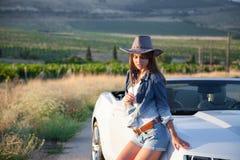 De tribunes van het cowboymeisje bij convertibel Stock Foto