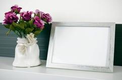 De tribunes van het fotokader op een plank naast de bloemen Royalty-vrije Stock Afbeelding