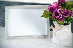 De tribunes van het fotokader op een plank naast de bloemen Stock Fotografie