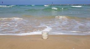 De tribunes van het koffieglas in nat zand dichtbij overzeese golven royalty-vrije stock afbeelding
