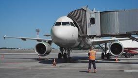 De tribunes van het passagiersvliegtuig op het platform vóór vertrek bij de telescopische ladder stock videobeelden