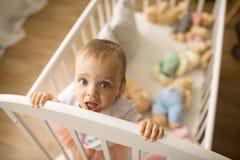 De tribunes van het peutermeisje in de voederbak onder het speelgoed stock afbeeldingen