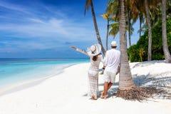 De tribunes van het reizigerspaar op een mooi, tropisch strand royalty-vrije stock fotografie