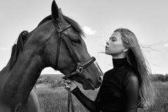 De tribunes van de meisjesruiter naast het paard op het gebied Het manierportret van een vrouw en de merries zijn paarden in het  royalty-vrije stock fotografie
