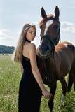 De tribunes van de meisjesruiter naast het paard op het gebied Het manierportret van een vrouw en de merries zijn paarden in het  stock afbeelding