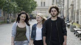 De triovrienden die op de straat lopen die verrassing met handgebaar en mond uitdrukken openden het zien van eng iets stock video