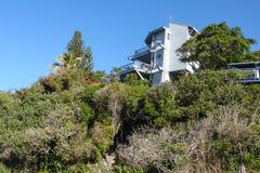 De tropische vegetatie behandelt een helling en bijna voert de huiden aan een huis van het drie verhaalstrand op de bovenkant van royalty-vrije stock afbeeldingen