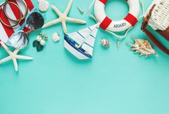 De tropische vlakte legt met strohoed, zak, zeester, shells, zonnebril, boot, oorringen op groene achtergrond De vlakte van de de stock fotografie