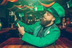 De trotse en zekere jonge mens zit bij lijst in bar Hij houdt mok donker bier en toont het aan camera Jonge mensenslijtage St stock foto's