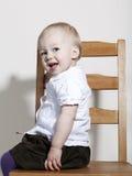 De trotse gelukkige zitting van het babymeisje op stoel Stock Fotografie