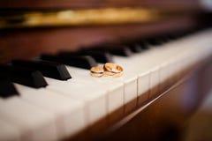 De trouwringen liggen op de pianosleutels stock fotografie