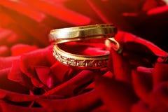 De trouwringen op rood namen toe Stock Foto