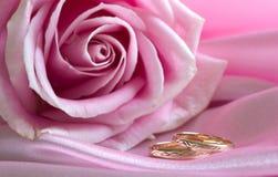 De trouwringen op roze met namen toe Stock Foto's
