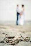 De trouwringen, overzeese kabel, cockleshells zijn op zand, silhouetten Stock Afbeeldingen