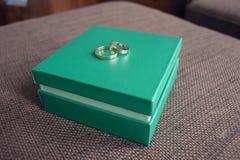 De trouwringen voor het jonggehuwdepaar liggen op een lichtgroene doos stock foto's