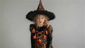 De truc of behandelt De partij van Halloween Het meisje toont de kwade tovenares Het kind draagt een een zwart-en-sinaasappelkled stock video