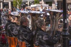 De tubamusici van een fanfarekorps die buiten in een vierkant van de stadsmarkt spelen en de toeschouwers bevinden zich het luist stock fotografie