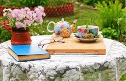 In de tuin is er een lijst voor ochtendthee en openluchtrecreatie stock afbeelding