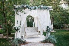 In de tuin is er een podium waarop een mooie witte bank in de stijl van de Provence of plattelander Boven de bank is een boog met stock afbeelding