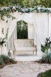 In de tuin is er een podium waarop een mooie witte bank in de stijl van de Provence of plattelander Boven de bank is een boog met royalty-vrije stock fotografie