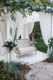 In de tuin is er een podium waarop een mooie witte bank in de stijl van de Provence of plattelander Boven de bank is een boog met stock fotografie