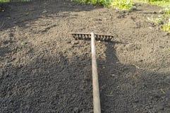 De tuin harkt het liggen op de geploegde bovengrond voor het planting-concept het tuinieren, de lente die, zonnelicht tuinieren royalty-vrije stock foto's
